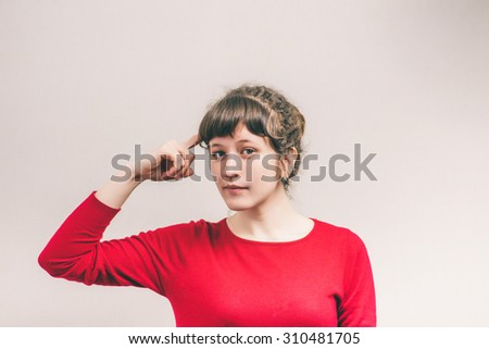 Woman thinking with finger to his temple. On a gray background. - stock photo