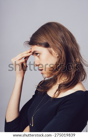 Woman thinking with his hand on his forehead. profile - stock photo