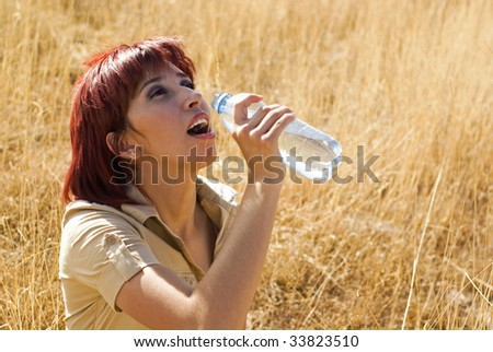 Woman thirsty enjoys drinking a bottle of water