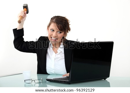 Woman threatening computer with hammer - stock photo