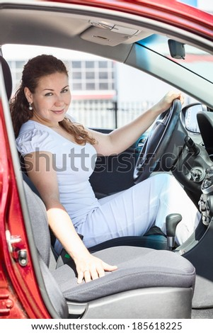 Woman through the opened door sitting in red car - stock photo