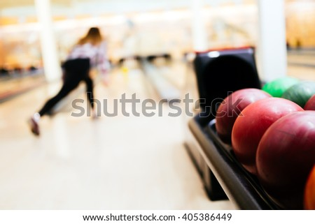 Woman throwing bowling ball in club - stock photo