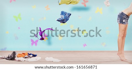 woman throwing clothes from wardrobe to the floor in sixties style - stock photo