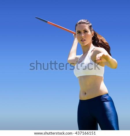 Woman throwing javeline against bright blue sky