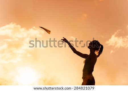 Woman throwing paper airplane in a beautiful setting.  - stock photo
