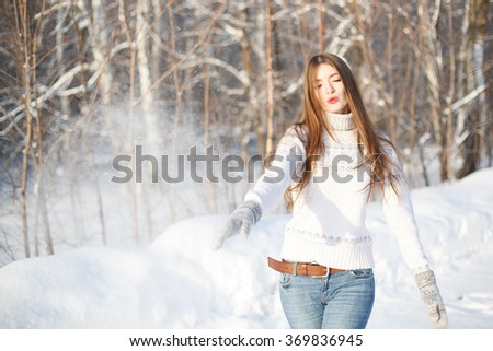 Woman throwing snowball. Flying Snowflakes. Sunny day. Joyful Beauty young woman Having Fun in Winter Park.  - stock photo