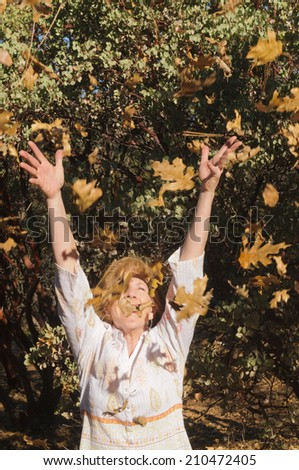 Woman throwing the autumn  falling leaves in the air - stock photo