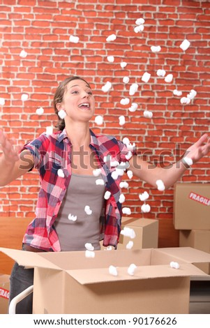 Woman throwing up packing peanuts - stock photo