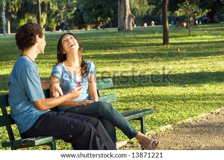 Woman throws back her head and laughs as her boyfriend gives her a red flower. Horizontally framed photograph.