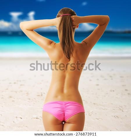 Woman topless on beautiful beach at Seychelles, Praslin, Anse Lazio. Collage. - stock photo
