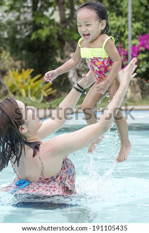 Woman tossing a little girl in the air. Fun in the swimming pool.