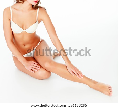 Woman touches her leg, white background, copyspace. - stock photo