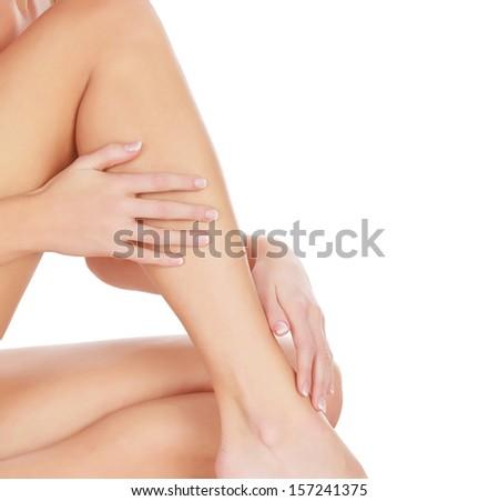 Woman touches her leg, white background, copyspace  - stock photo