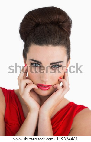 Woman touching her face and looking serious while having beehive hairstyle - stock photo