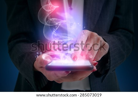 woman touching smartphone and shiny magic comes from screen - stock photo