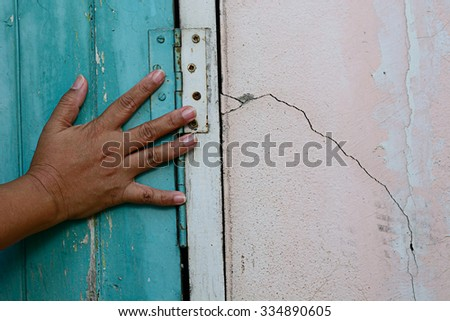 Woman touching the wall, Aged wooden door with rusty hinges and shows structural damage wall crack