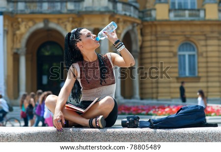 woman tourist drinking from bottle and relaxing - stock photo