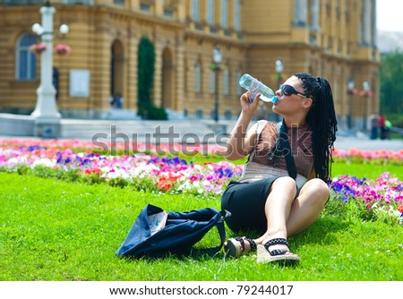 woman tourist drinks water from plastic bottle in old city - stock photo