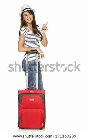 Woman tourist. Full length happy young woman standing with suitcase and pointing at the copy space, isolated on white background - stock photo