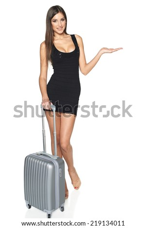 Woman tourist. Full length sexy young woman in black mini dress standing with suitcase and showing blank copy space, isolated on white background - stock photo
