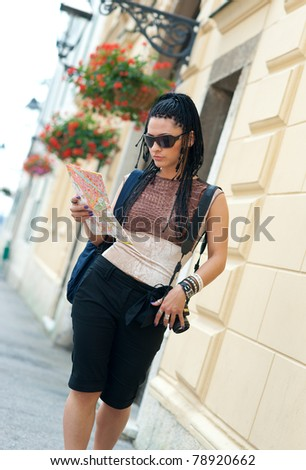 woman tourist holding map and walking in the city street - stock photo