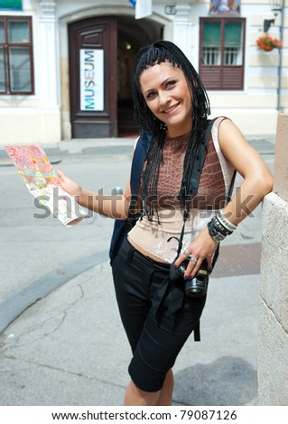woman tourist holding map at the museum building - stock photo