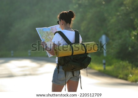 Woman tourist in nature read the map - stock photo