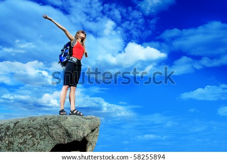 Woman tourist is standing at the top of a mountain with a feeling of freedom. - stock photo