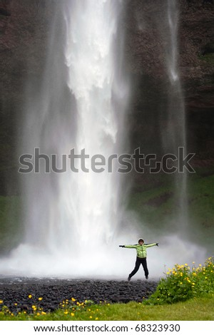 woman tourist jumping in front of Seljalandsfoss waterfall, Iceland - stock photo