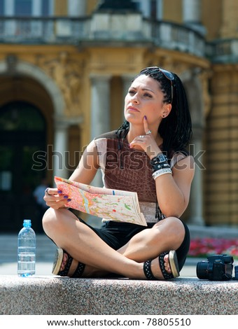 woman tourist looking at map and thinking in old city site - stock photo