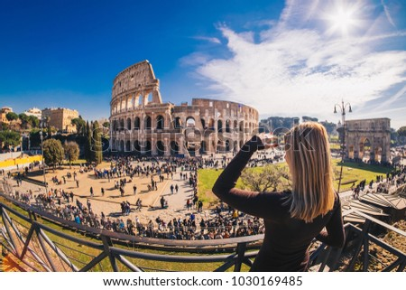 Woman tourist looking at the Roman Colosseum in Rome, Italy