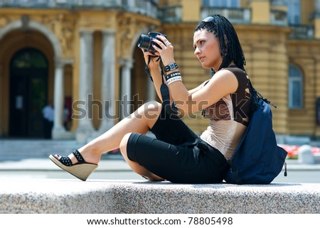 woman tourist looking photos at her camera display - stock photo