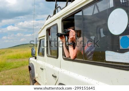 Woman tourist on safari in Africa, travel in Kenya, watching wildlife in savanna with binoculars  - stock photo