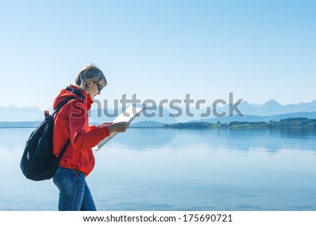 Woman tourist reading the map, during travel in Norway against blue hazy mountains background - stock photo