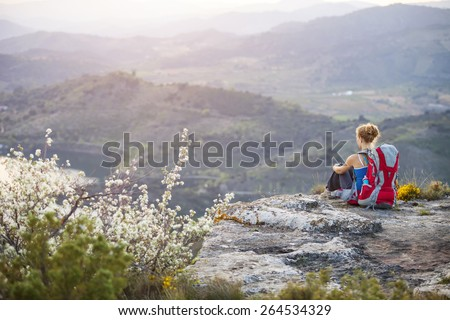 Woman tourist sitting on top of a mountain  - stock photo