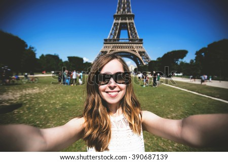 Woman tourist smiling and making travel selfie. Beautiful European girl enjoying vacation in Paris, France - stock photo