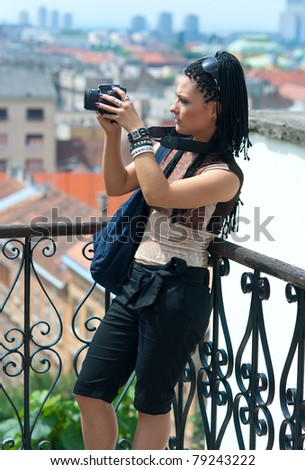 woman tourist standing at city panoramic view with camera - stock photo