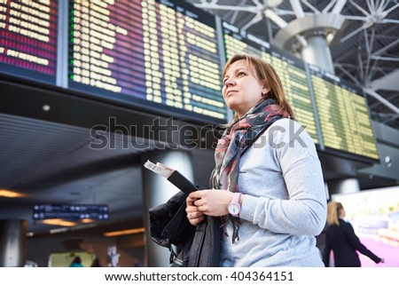 Woman tourist standing at the airport on the background of departures and arrivals - stock photo