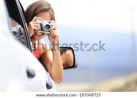 Woman tourist taking photo in car with camera driving on road trip travel vacation. Girl passenger taking picture out of window with vintage retro camera. - stock photo