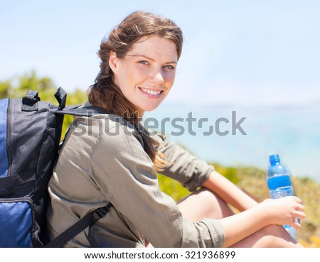 Woman tourist with backpack drinking water in nature - stock photo
