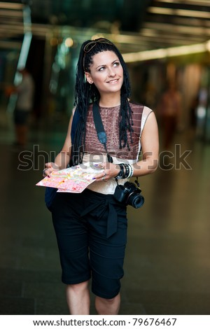woman tourist with map walking in the city street by night - stock photo