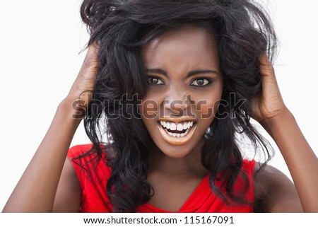 Woman tousling her curly hair on white background