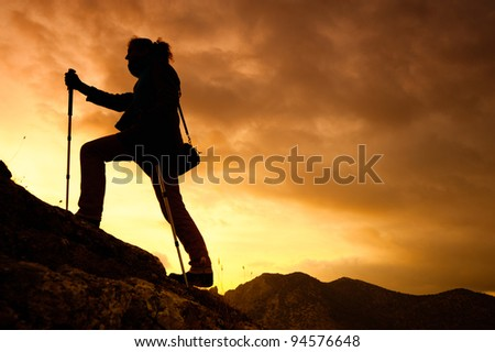 woman tracking sticks up on the mountain, hiking trips in the mountains - stock photo