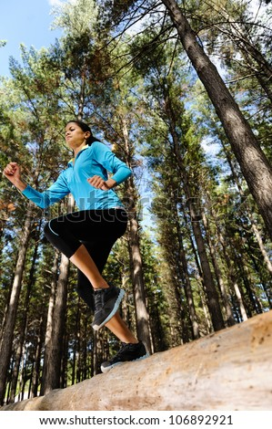 Woman trail running in the woods and jumping over logs while on extreme outdoor fitness training in forest. - stock photo