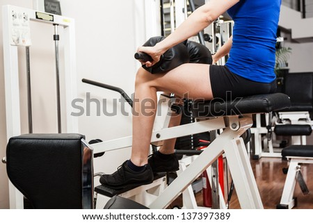 Woman training her legs in a fitness club - stock photo