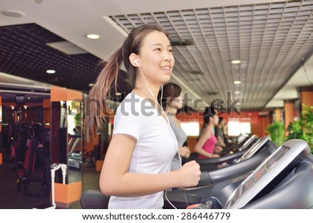 Woman training in a fitness club. While running while using headphones to listen to music - stock photo