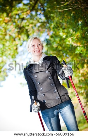 Woman training Nordic Walking in autumn scenery - stock photo