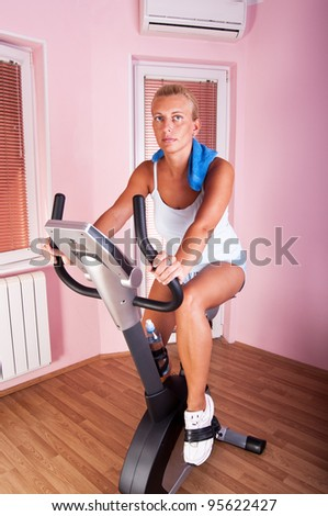 Woman training on exercise bike at home - stock photo