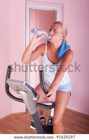 Woman training on exercise bike at home, drinking water - stock photo