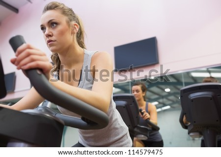 Woman training on exercise bike in a spinning class in gym - stock photo